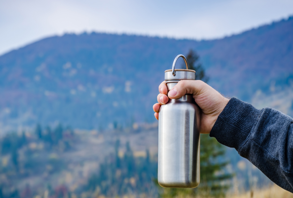 man holding silver water bottle on mountain